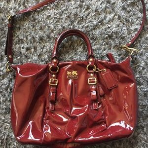 Shiny red/burgundy leather coach purse.